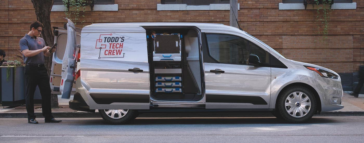 A silver 2021 Ford Transit Connect van is shown from the side with the side and rear doors open.