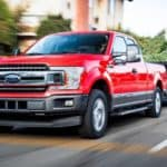 A red 2020 Ford F-150 with a Powerstroke diesel engine is towing a trailer full of trees on a city street.
