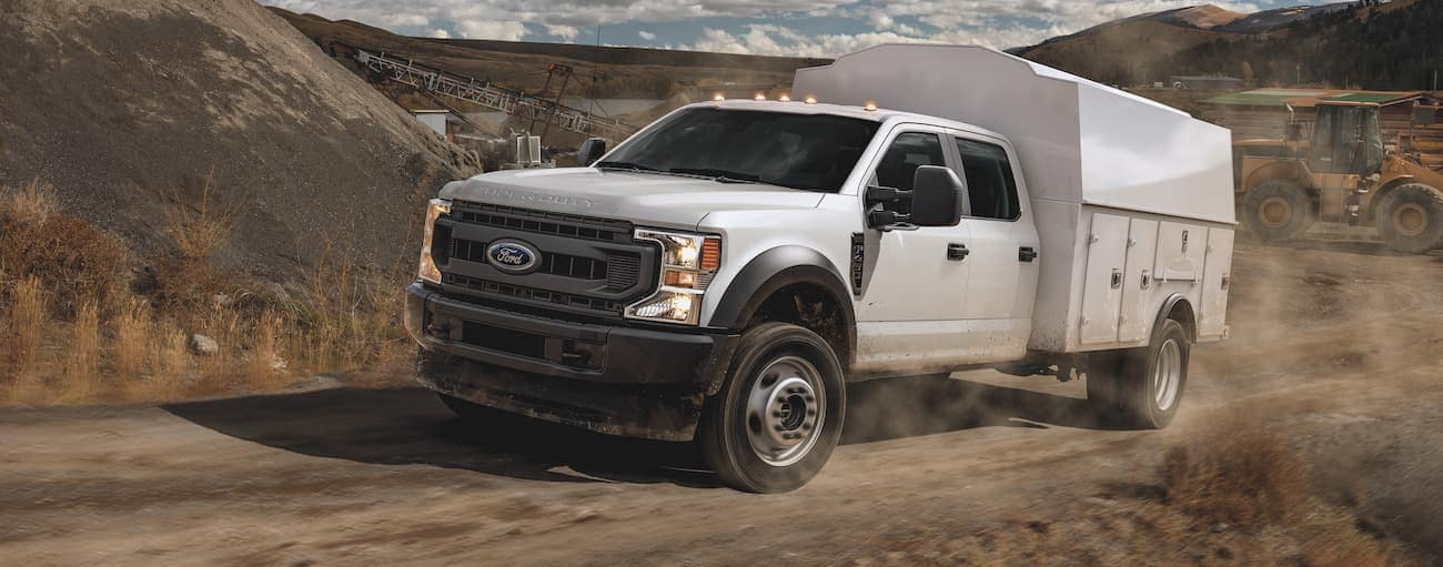 A white 2012 Ford F-450 with a utility upfit is driving on a dirt road through hills.