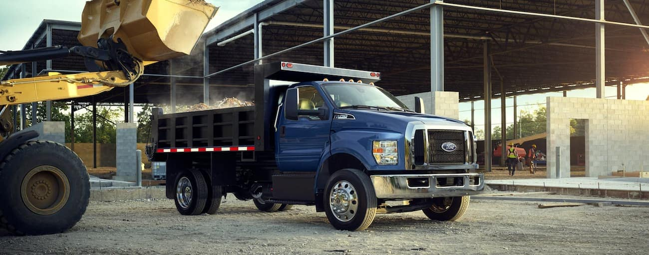 A blue 2021 Ford F-750 with a dump bed is at a building site.