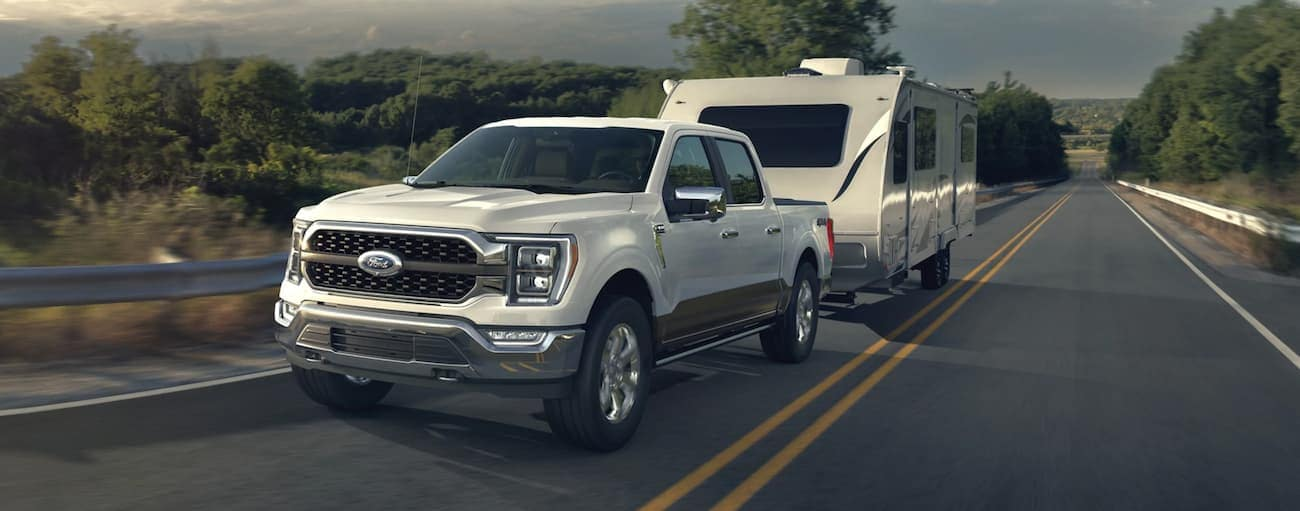 A white 2021 Ford F-150 is towing a camper uphill.
