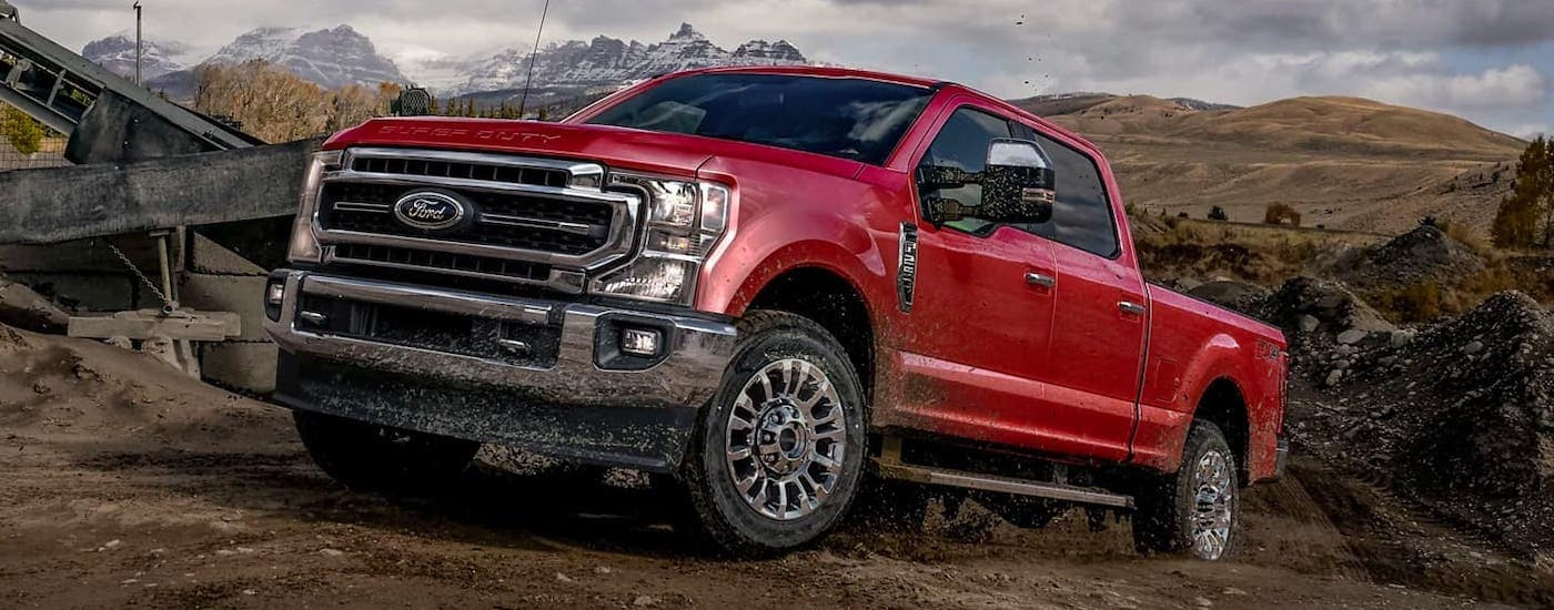A red 2021 Ford F-250 is driving on a trail and covered in mud.