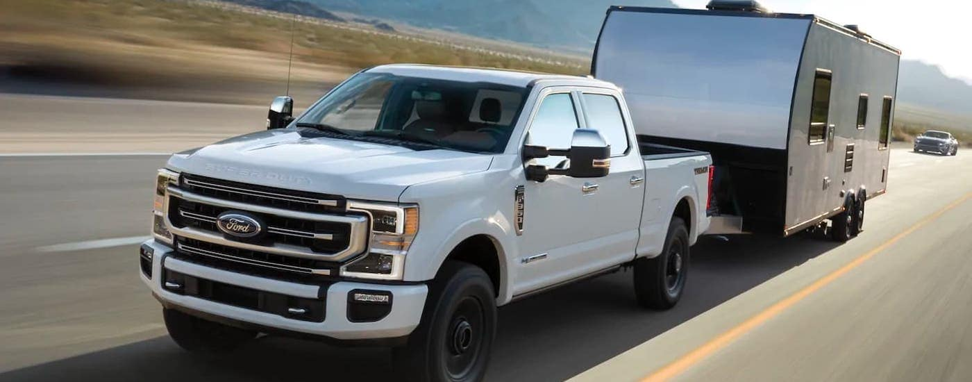A popular Ford diesel truck, a white 2021 Ford F-350, is towing a trailer on an empty highway.