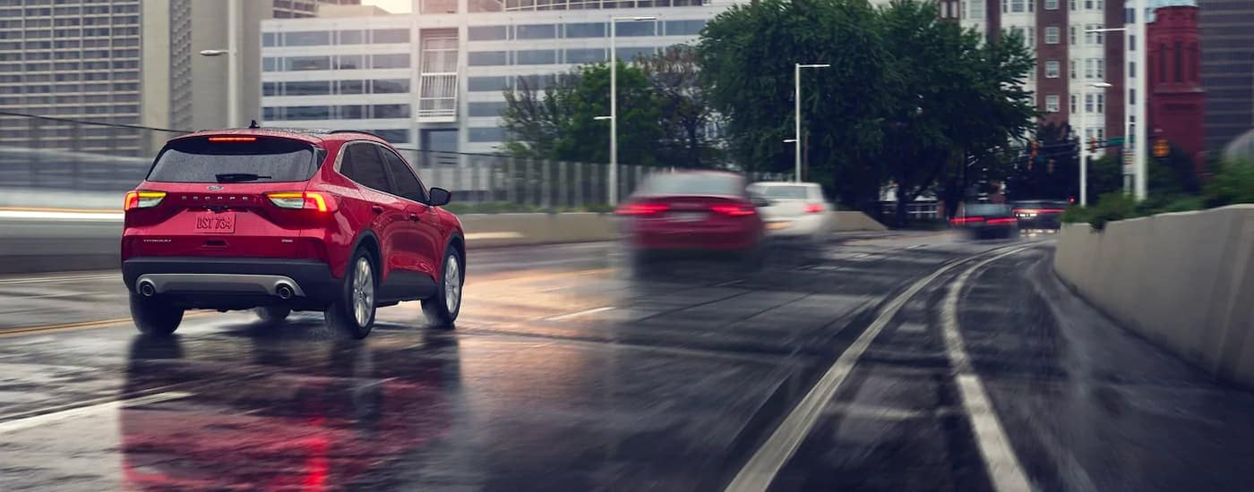 A red 2021 Ford Escape is driving down a wet road in to the city.