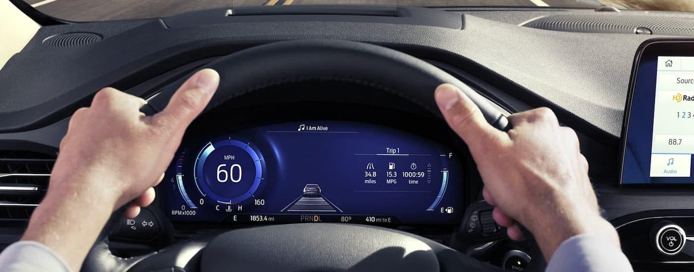 A close up is shown of the steering wheel and gauge cluster on a 2021 Ford Escape.