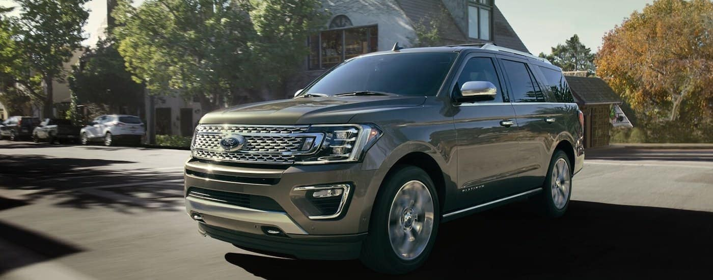 A grey 2021 Ford Expedition is shown driving through the suburbs.