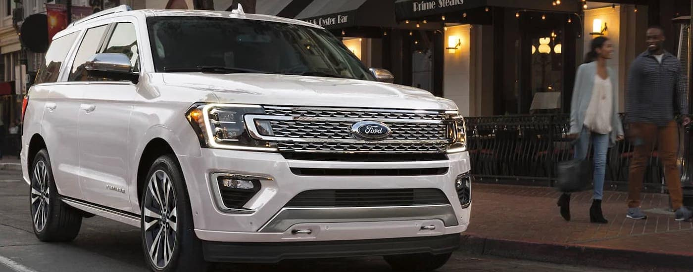 A white 2021 Ford Expedition is parked on a city street after winning the 2021 Ford Expedition vs 2021 Chevy Tahoe comparison.