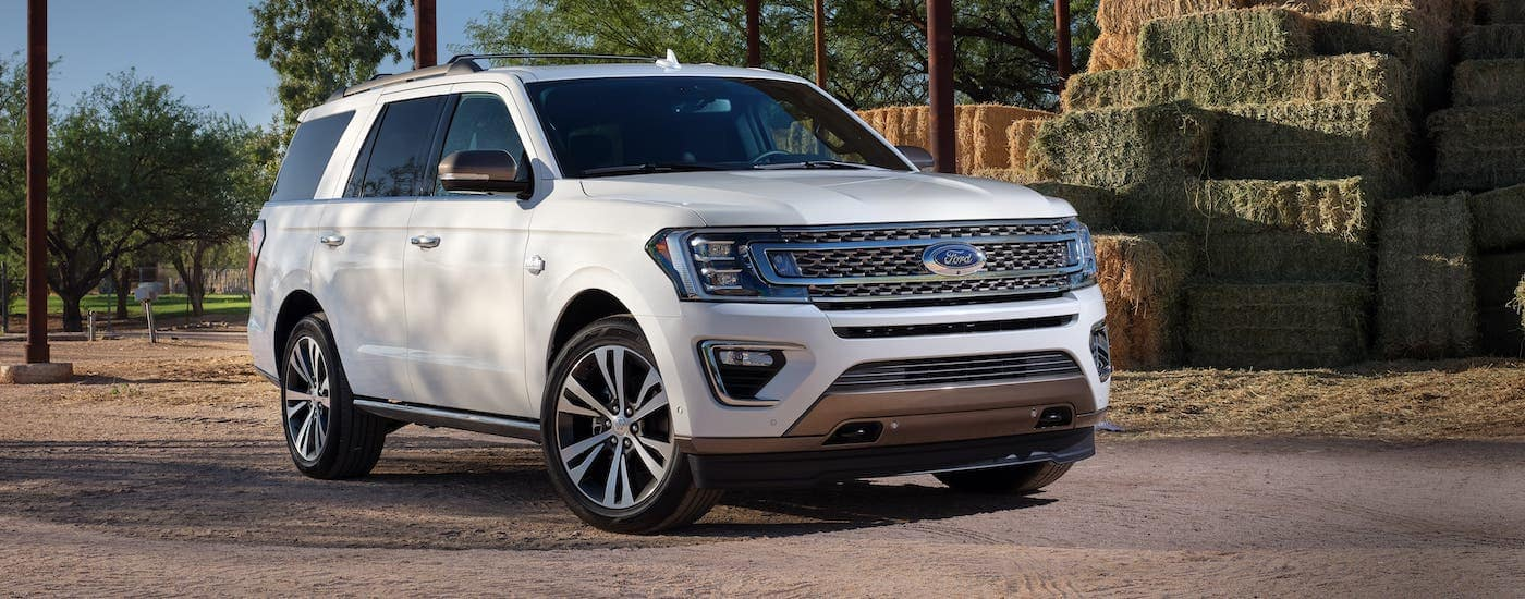 A white 2020 Ford Expedition King Ranch is parked in front of hay bales.