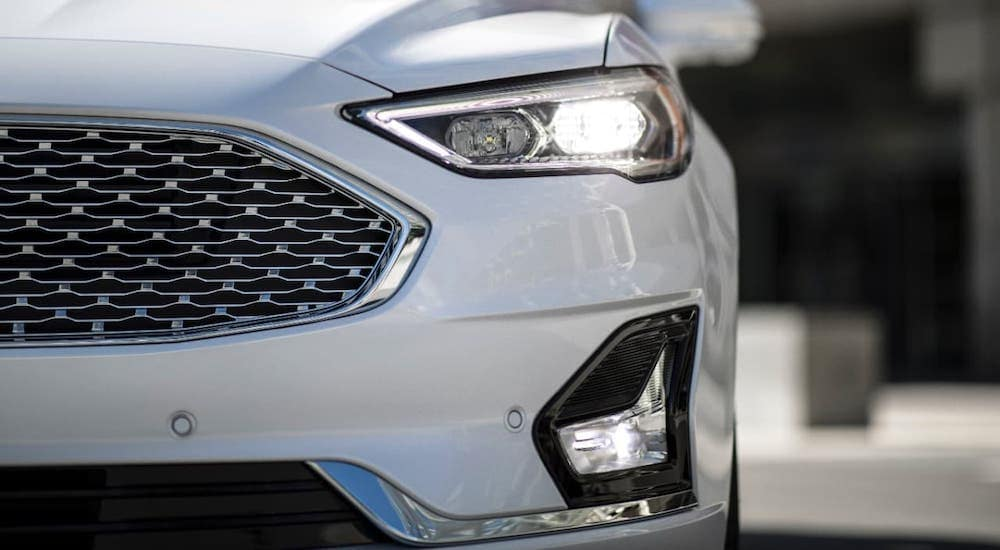 A closeup shows the grille of a white 2020 Ford Fusion at an Albany car dealer.