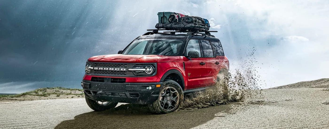 A red 2021 Ford Bronco Sport with cargo on the roof is driving on sand.