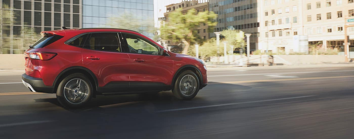 A red 2021 Ford Escape is driving on a city street and shown from the side.