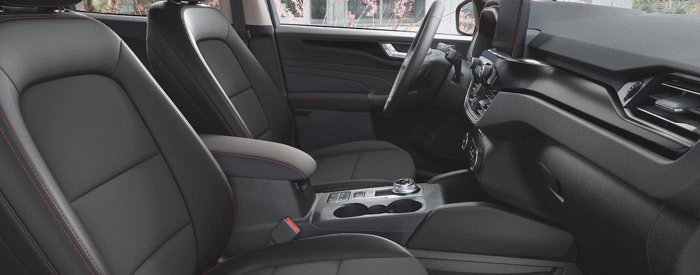 The black front seats with red accent stitching is shown from the passenger seat in a 2021 Ford Escape.