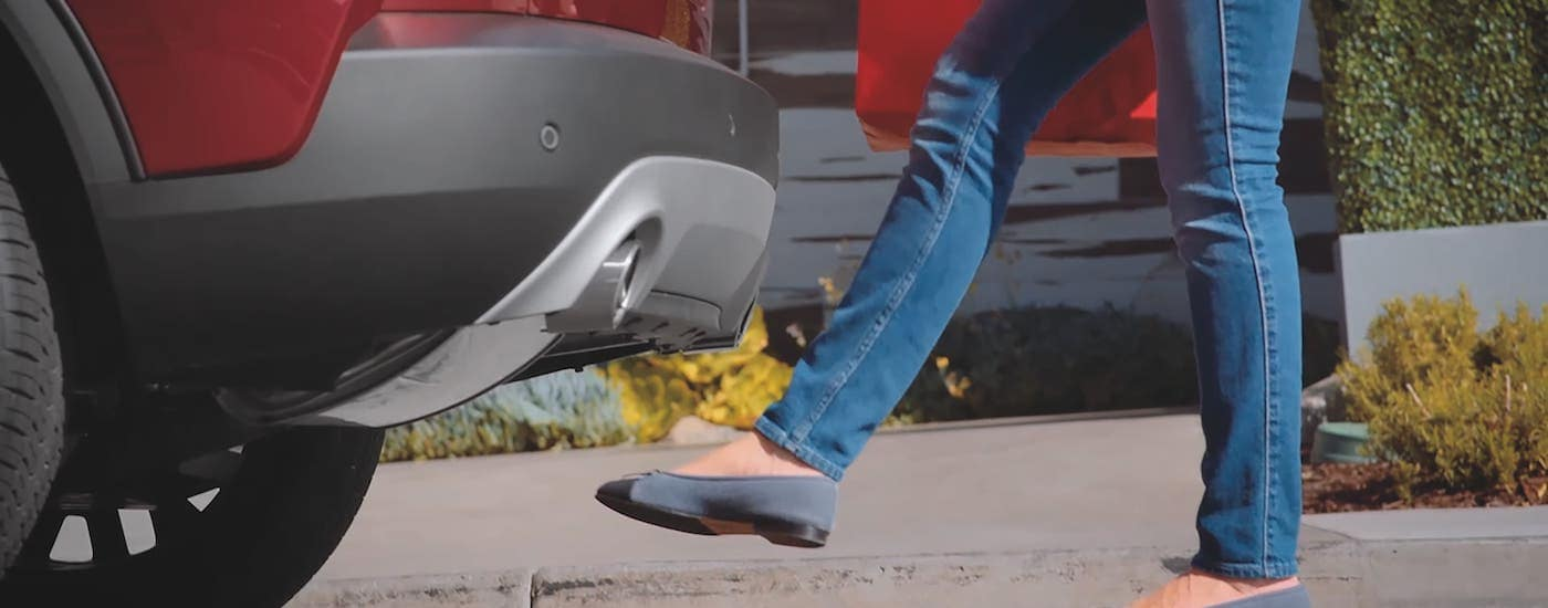 A closeup shows a foot waving under the rear of a red 2021 Ford Escape to open the liftgate.