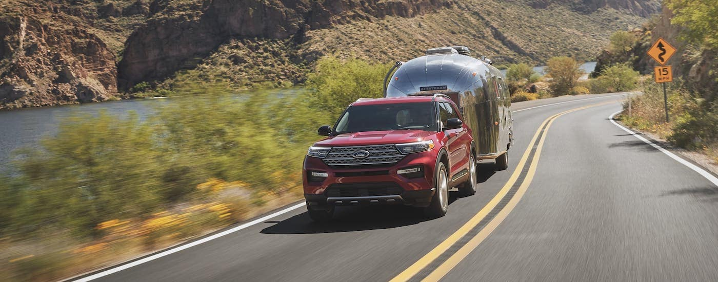 A red 2021 Ford Explorer is shown from the front towing an Airstream camper.