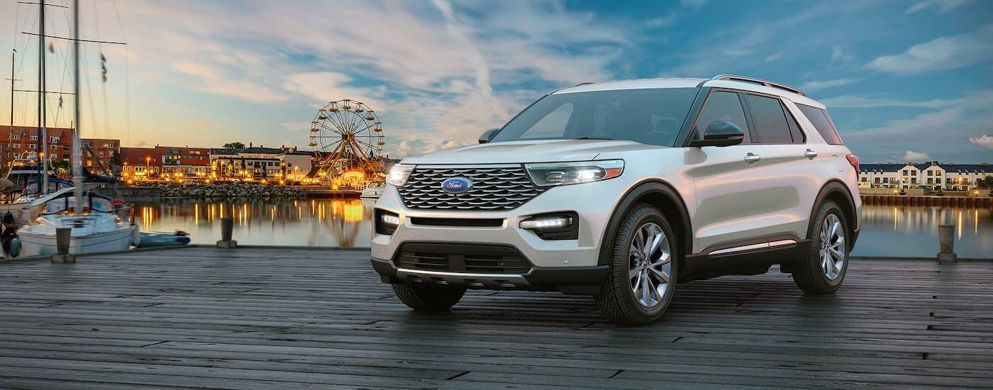 A white 2021 Ford Explorer is parked on a pier in front of a carnival.