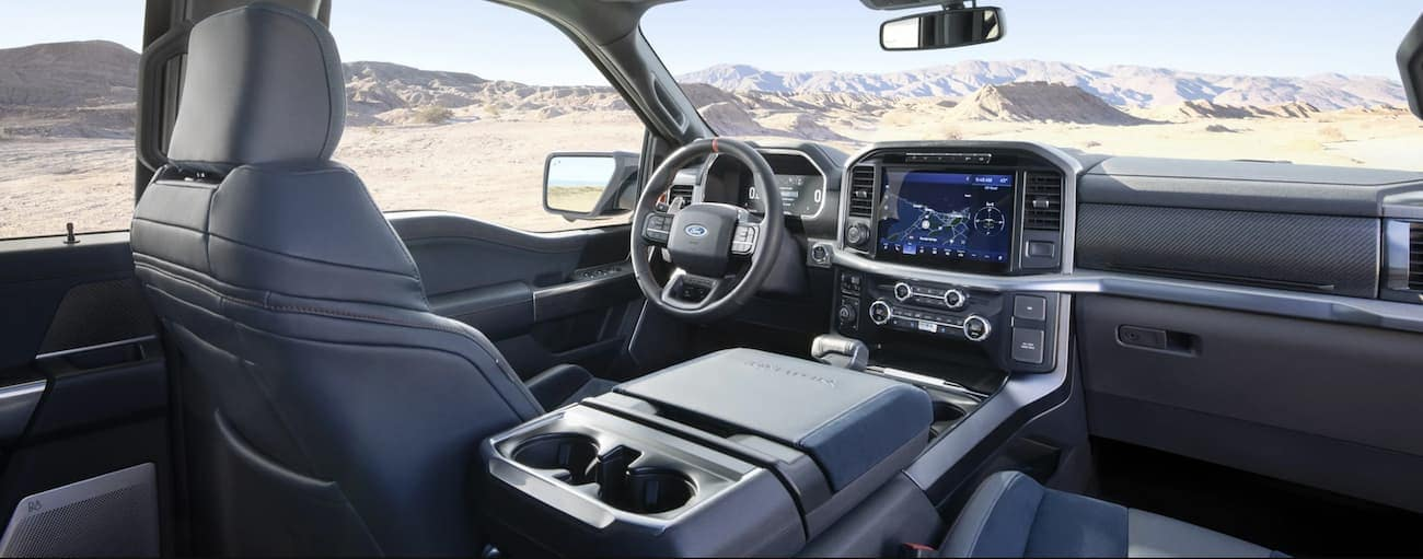 The grey interior is shown inside a 2021 Ford F-150 Raptor with mountains in the window.