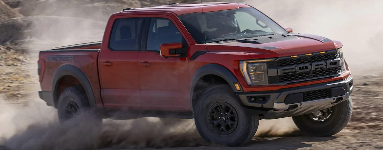 A red 2021 Ford F-150 Raptor is off-roading in dirt after winning the 2021 Ford F-150 Raptor vs 2021 Ram 1500 TRX comparison.