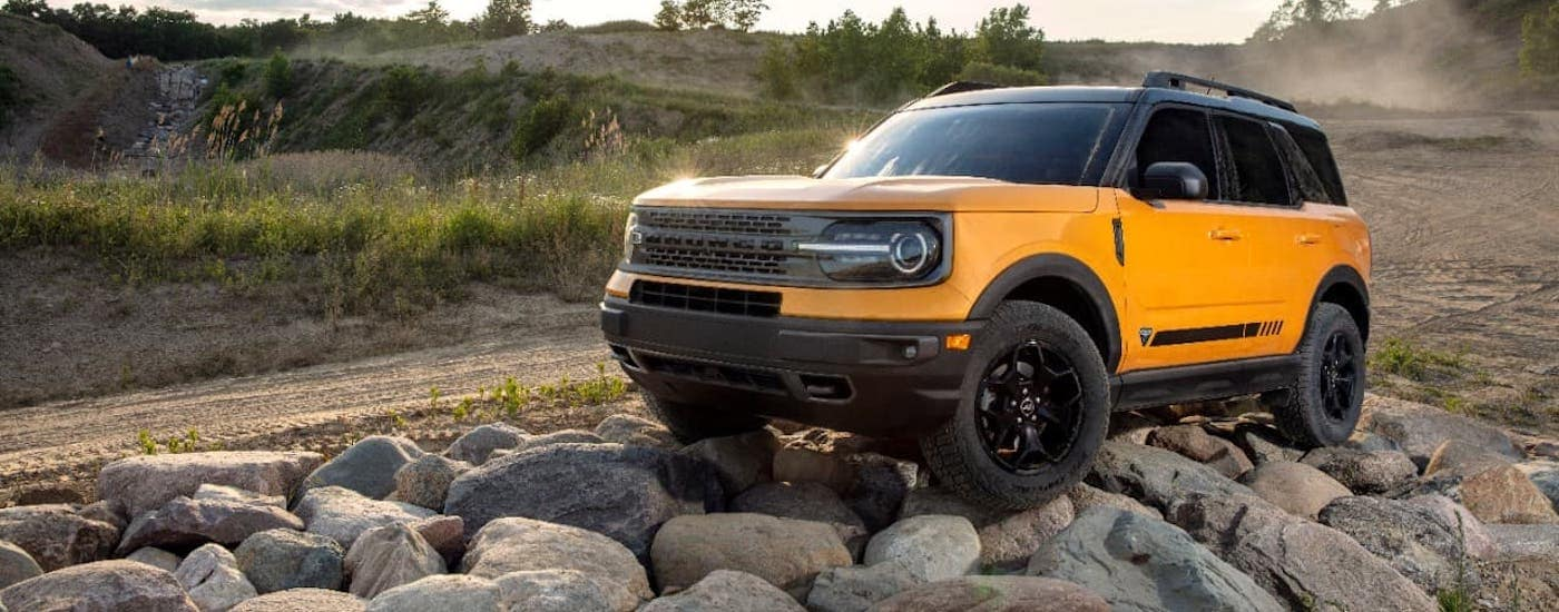 A yellow 2021 Ford Bronco Sport is climbing over rocks next to a dirt trail.