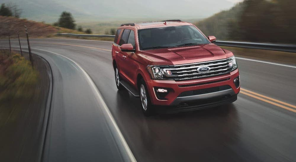 A red 2021 Ford Expedition is driving on a winding highway.
