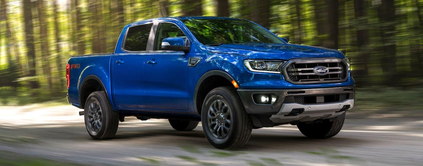 A blue 2021 Ford Ranger is driving on a road through the woods after leaving a Ford dealer near Troy.
