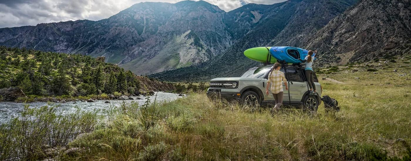 A pale green 2021 Ford Bronco Sport is shown from the side next to a river after winning the 2021 Ford Bronco Sport vs 2021 Toyota RAV4 comparison.