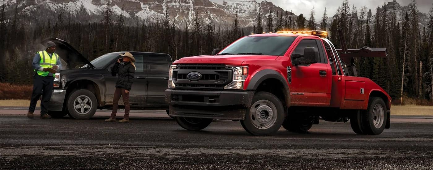 A red 2021 Ford Chassis Cab F-450 is shown from the side parked next to a broken down black truck.