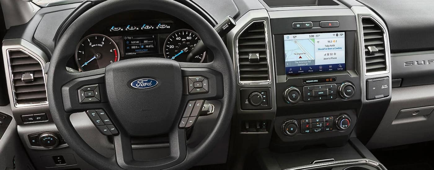 The steering wheel and infotainment screen are shown on a 2021 Ford Chassis Cab.