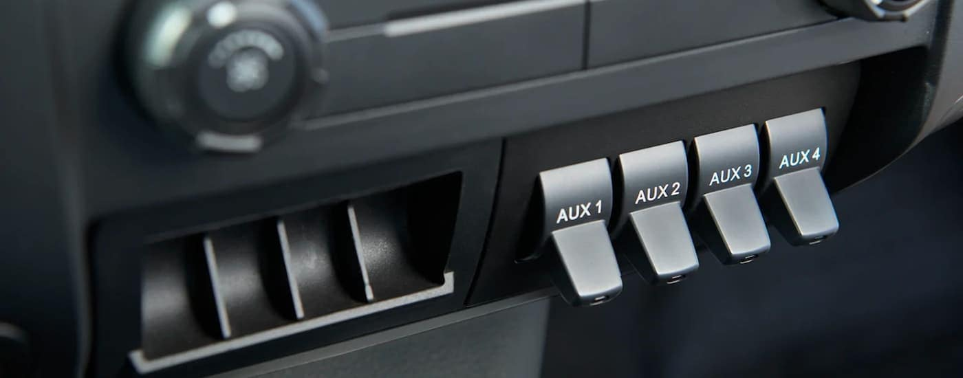 A close up shows the black interior and multiple auxiliary ports on a 2021 Ford F-650.