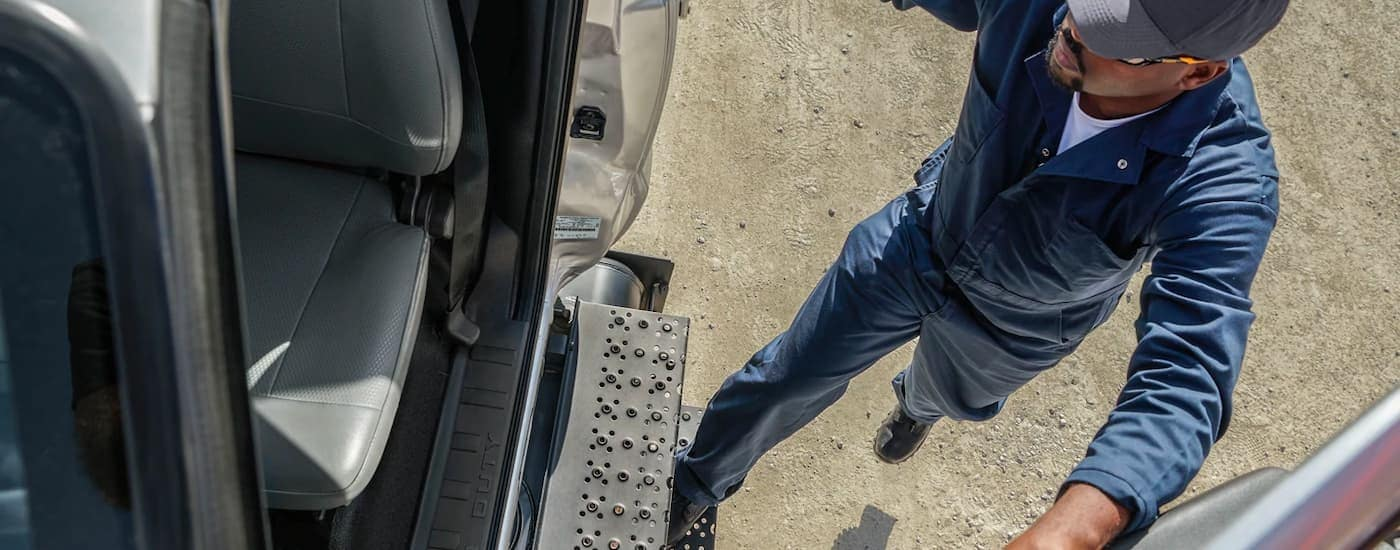 A close up view from a high angle shows a worker in a blue jumpsuit using the step plate to get in a 2021 Ford F-650.
