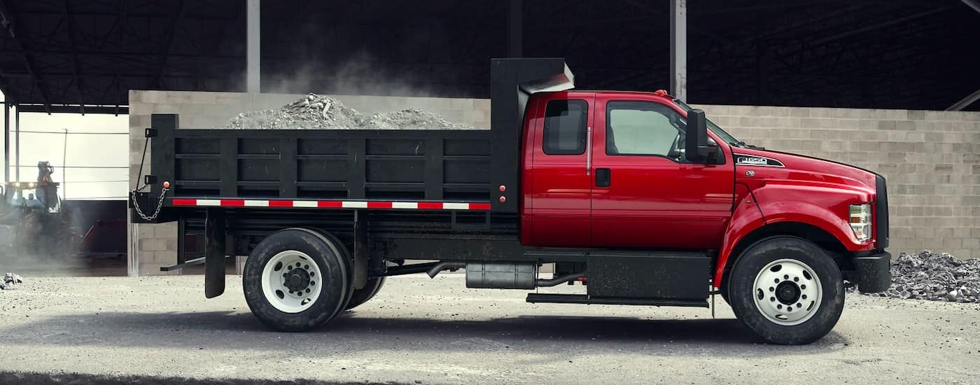 A red 2021 Ford F-650 is shown from the side with a dump body after winning the 2021 Ford F-650 vs 2021 Ford F-750 comparison.