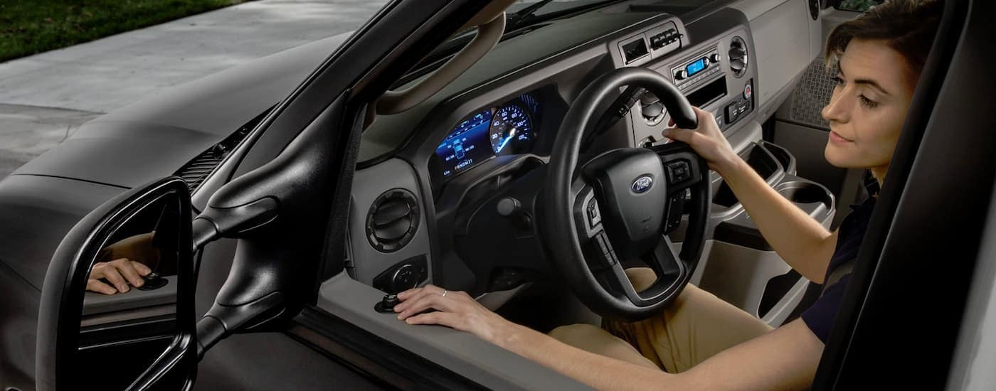 A close up shows a woman looking in the side mirror of a black 2022 Ford E-Series Cutaway.