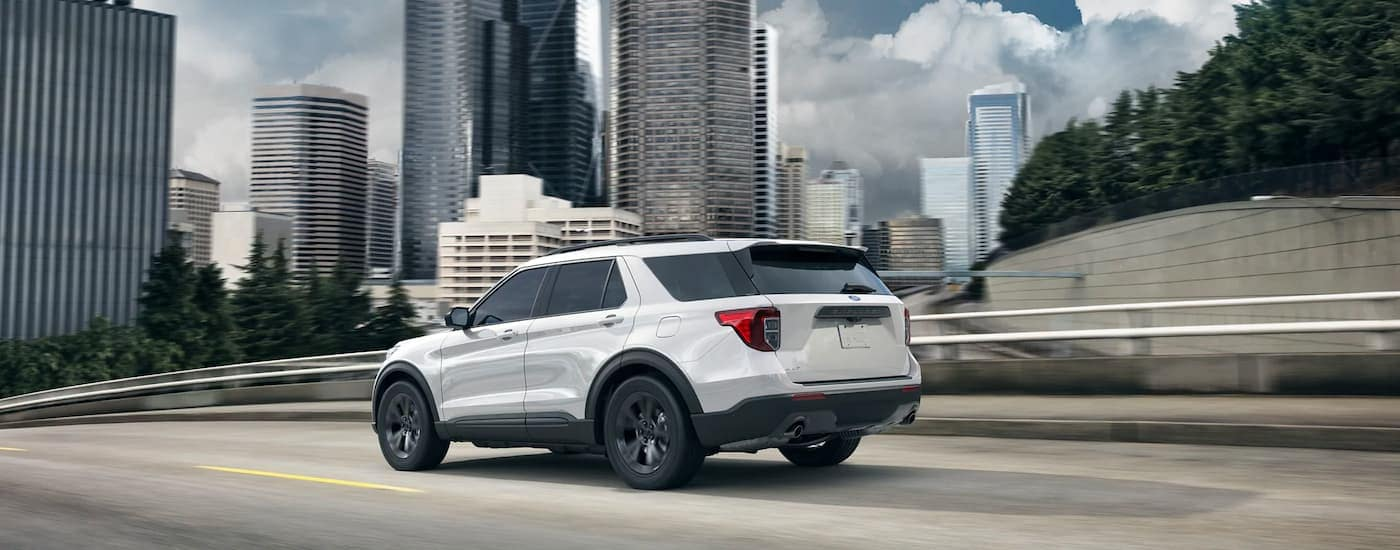 A white 2021 Ford Explorer is driving past a city after winning the 2021 Ford Explorer vs 2021 Chevy Traverse comparison.