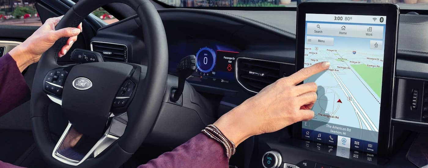 A close up shows a woman making a selection on the infotainment screen in a 2021 Ford Explorer.