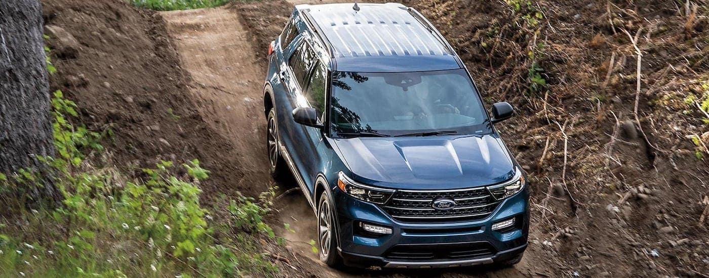 A dark blue 2021 Ford Explorer is shown speeding down a dirt hill.