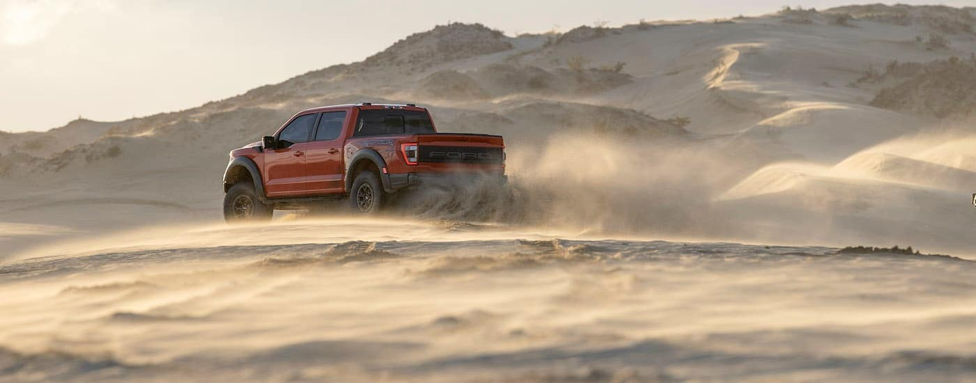 A red 2021 Ford F-150 Raptor is shown from the side driving through the dirt while kicking up dust.