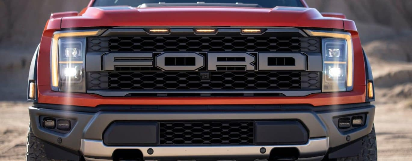 A close up shows the front grill on a red 2021 Ford F-150 Raptor.