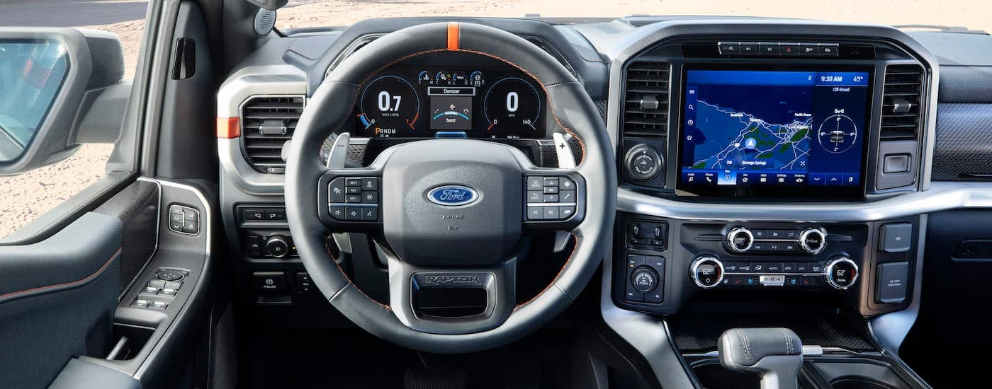 The black and silver steering wheel and infotainment screen are shown in a 2021 Ford F-150 Raptor.