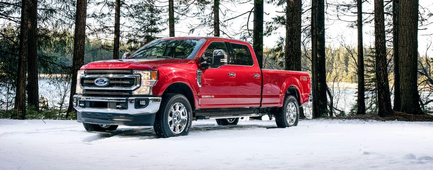 A red 2021 Ford F-250 King Ranch is parked the snow in the woods.