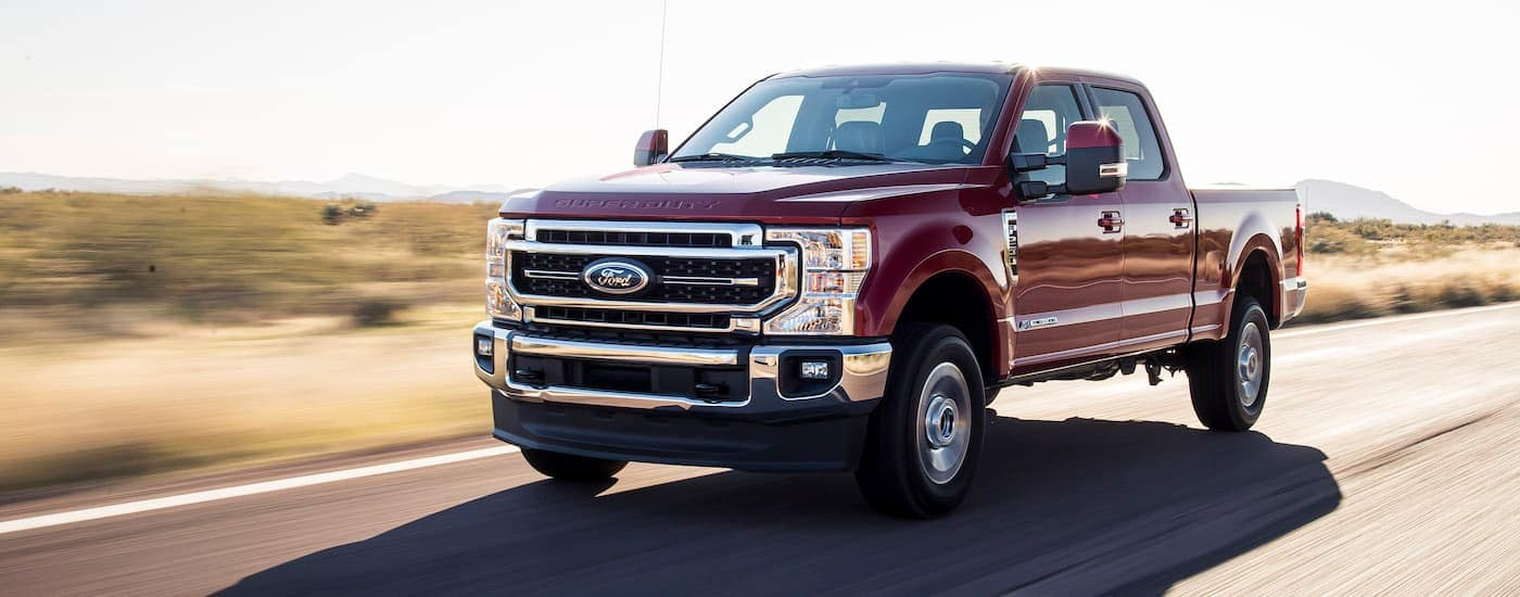A maroon 2021 Ford F-250 Lariat Ultimate is shown from the side driving down an empty highway.