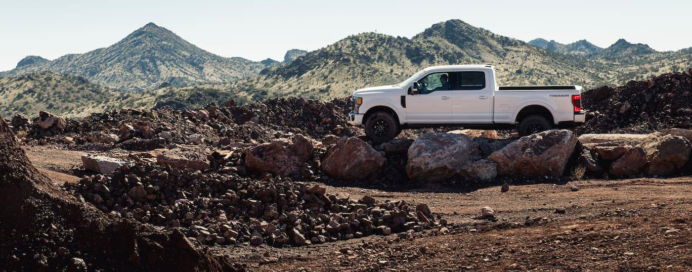 A white 2021 Ford F-250 Tremor Sport is parked on a dirt pile with mountains in the distance.