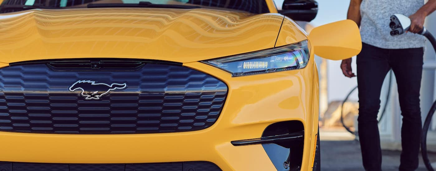 A close up shows the front end of a 2021 Ford Mustang Mach-E while a person approaches it with a charger.