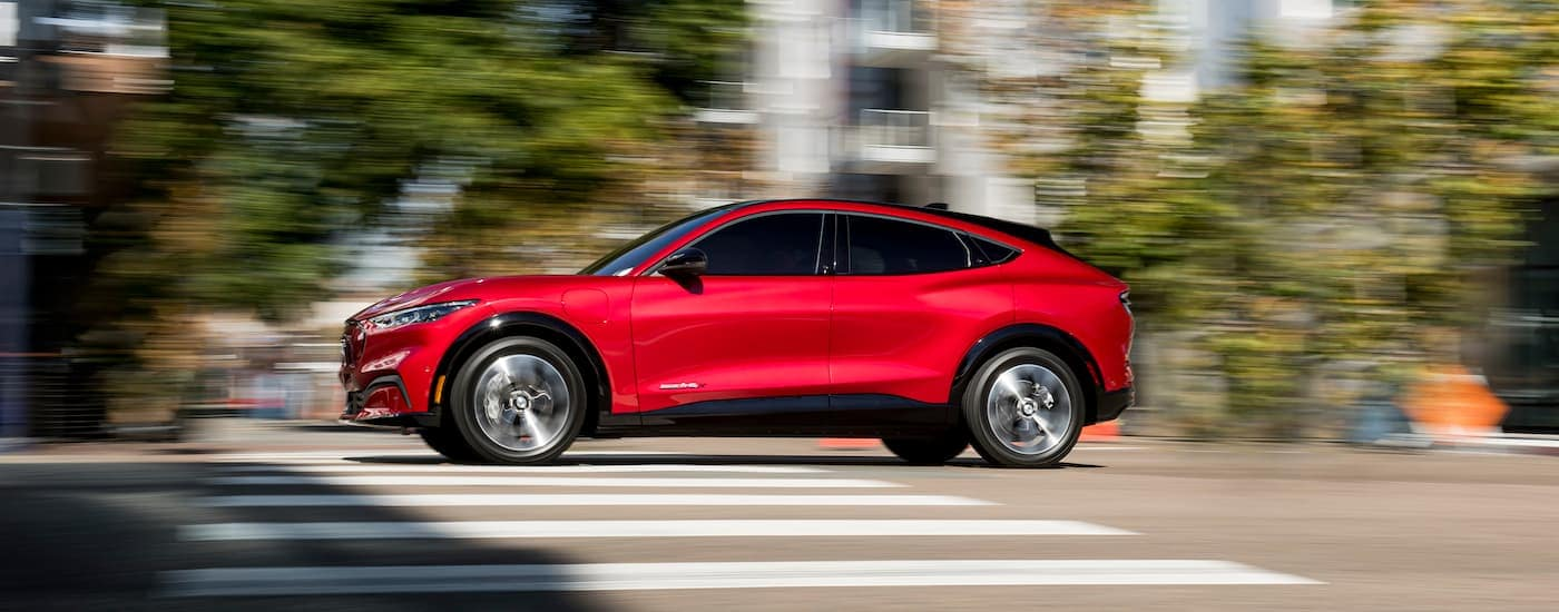 A red 2021 Ford Mustang Mach-E is shown from the side speeding down the road after winning the 2021 Ford Mustang Mach-E vs 2022 Chevy Bolt EUV comparison.