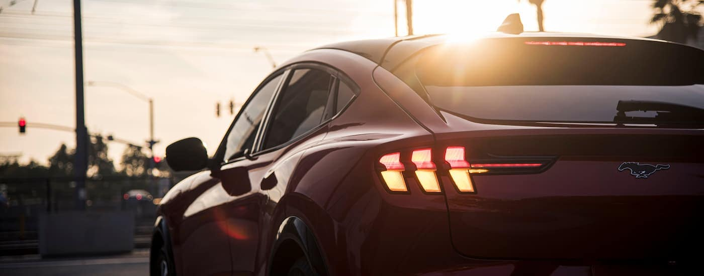 A red 2021 Ford Mustang Mach-E is shown from the rear with the sun setting over the city.
