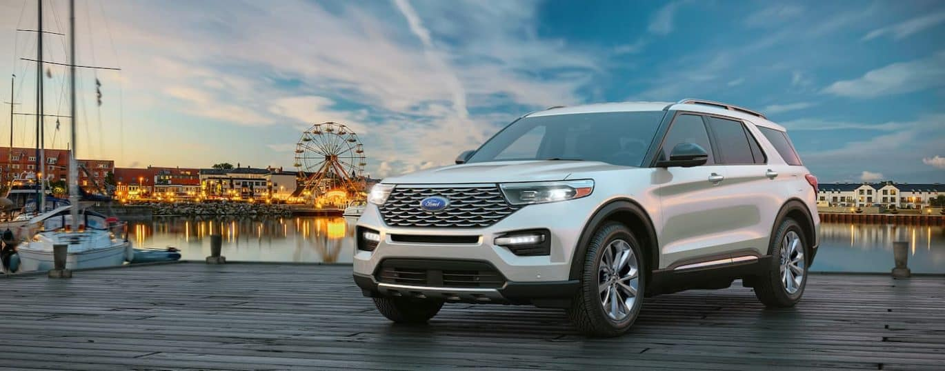 A white 2021 Ford Explorer is shown with an amusement park and lake in the background.