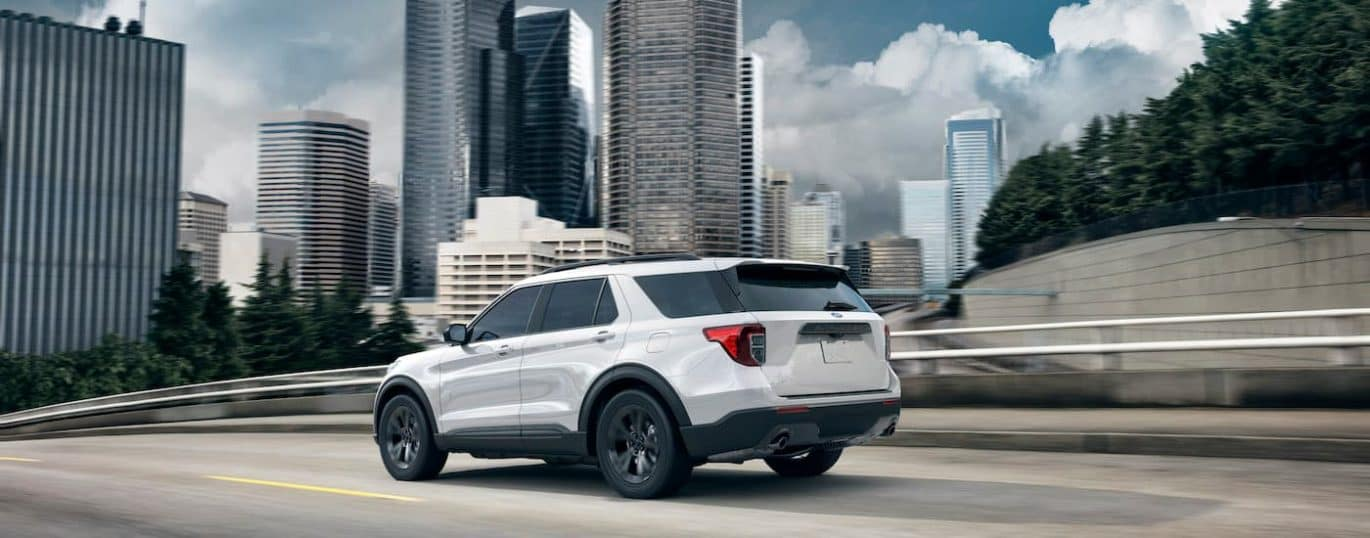 A white 2021 Ford Explorer is shown from the side driving past a city after winning the 2021 Ford Explorer vs 2021 Jeep Grand Cherokee comparison.