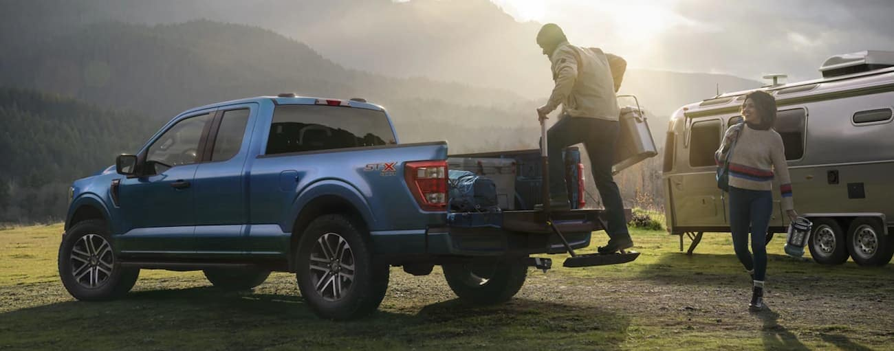 A person is loading the bed of a blue 2021 Ford F-150 using the tailgate step while parked next to an Airstream in front of mountains.