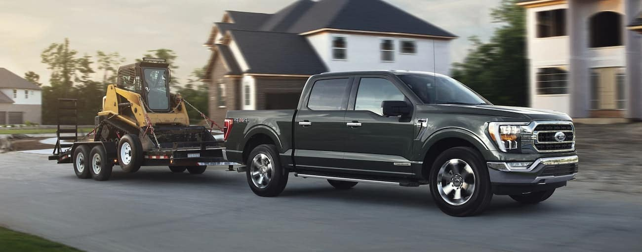 A dark grey 2021 Ford F-150 is towing machinery in a neighborhood development after winning the 2021 Ford F-150 vs 2021 GMC Sierra 1500 comparison.