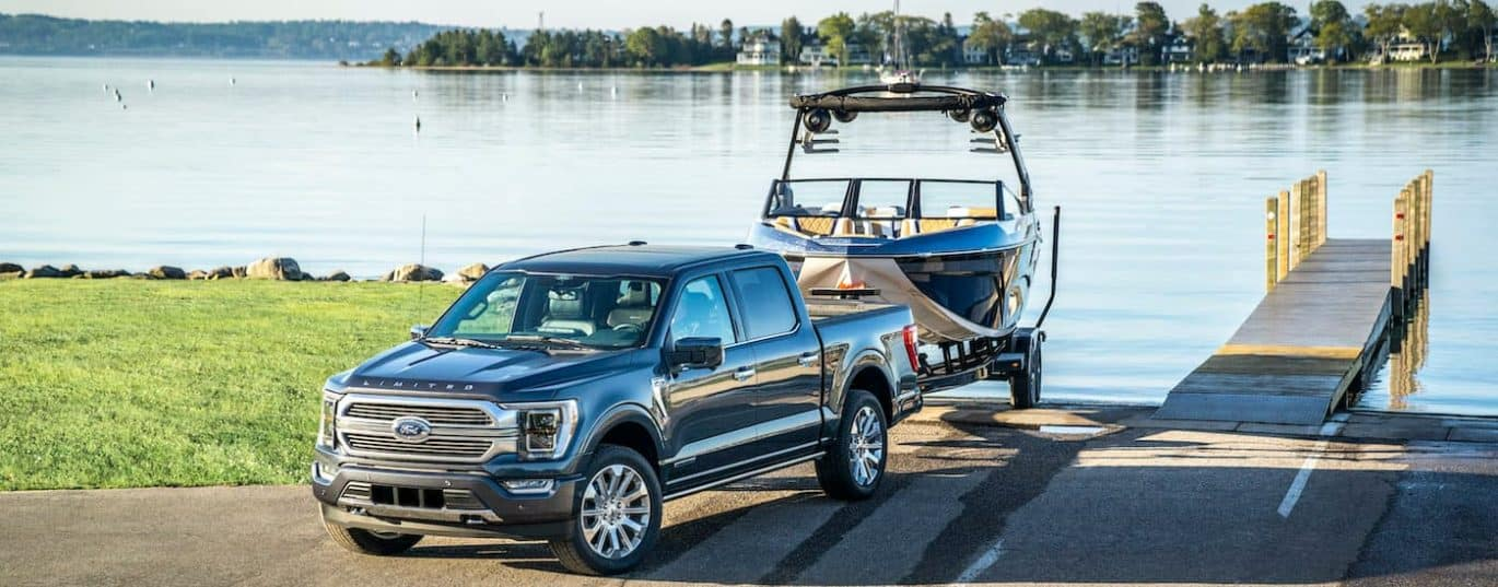 A black 2021 Ford F-150 is shown backing a boat into a lake after winning the 2021 Ford F-150 vs 2021 Nissan Titan showdown.