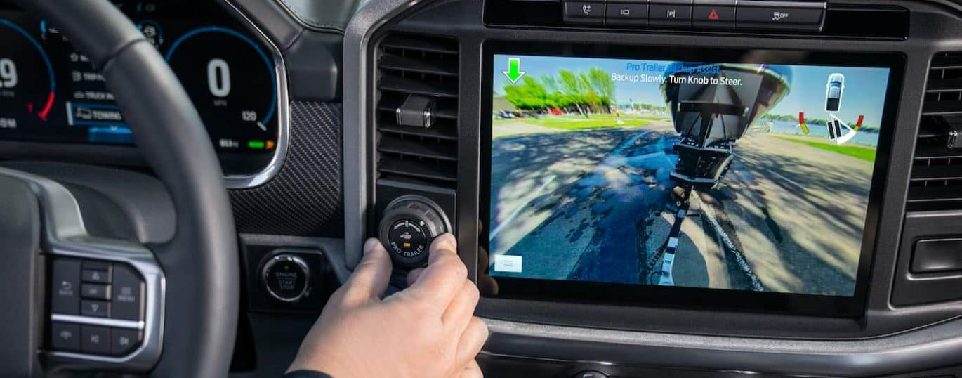 A close up shows the infotainment screen and back up camera view in a 2021 Ford F-150.