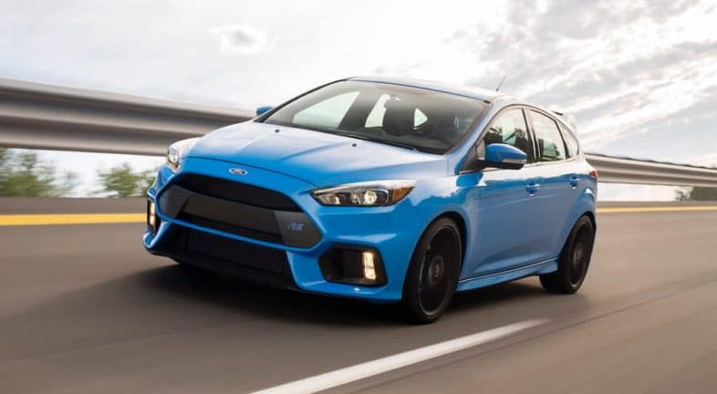 A blue 2016 Ford Focus RS is driving on a highway after leaving a used Ford Focus dealer.